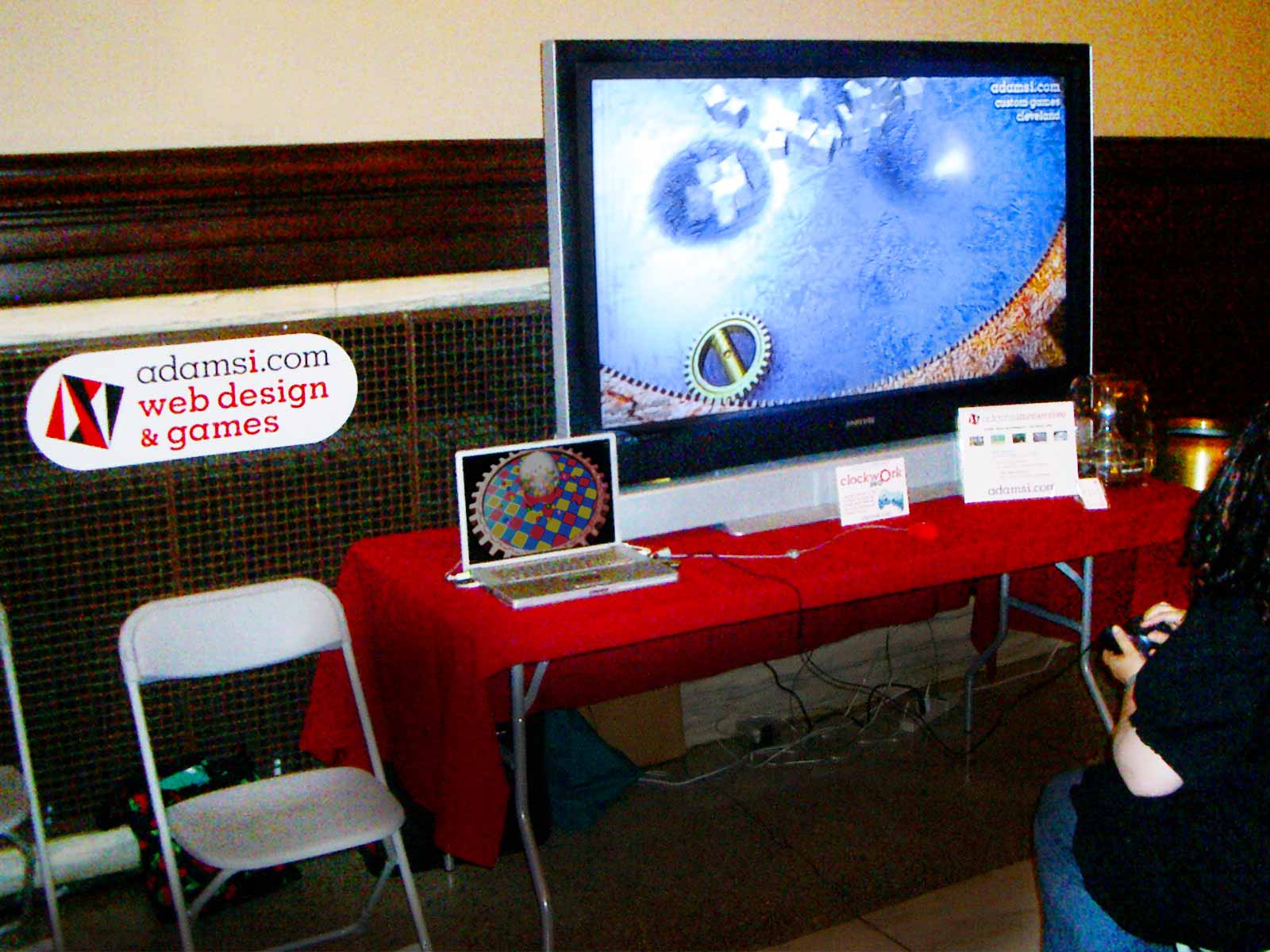 Photo: woman with gamepad playing Mac game on large screen at technology festival