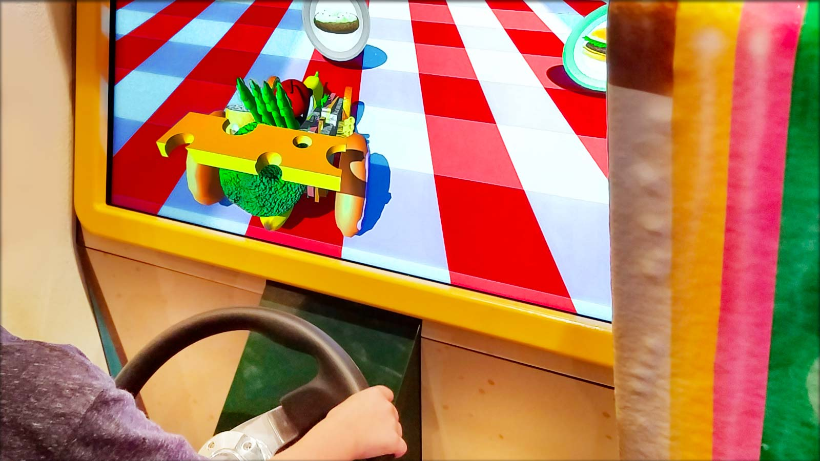 Photo: child using a steering wheel to play driving game in a museum, with a car and obstacles made of food